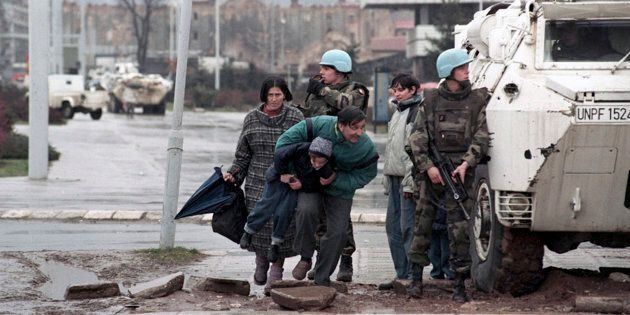 The residents of Sarajevo take cover from sniper fire behind a United Nations Protection Force (UNPROFOR)...