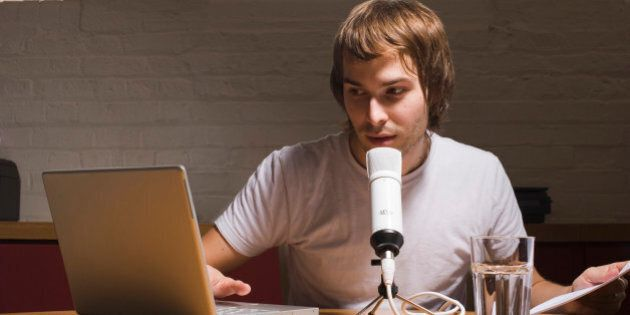 Young man with laptop and microphone,