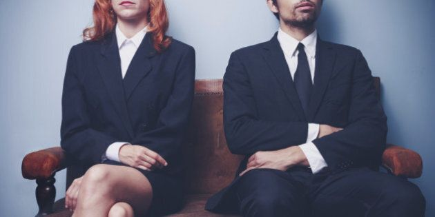 Two sharply dressed business people are waiting on a sofa with a serious expression on their faces. Maybe...