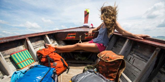 A woman with multiple bags traveling on a long-tail boat in