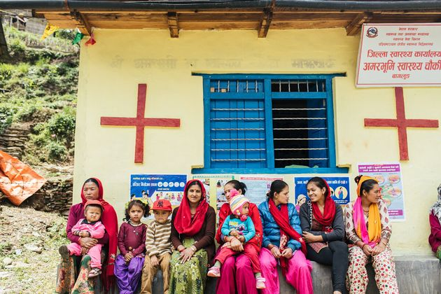 Mothers sit outside a birthing clinic,