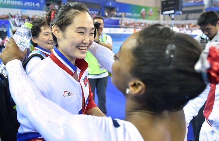 Hong Un Jong of North Korea is congratulated by U.S. gymnast Simone Biles.