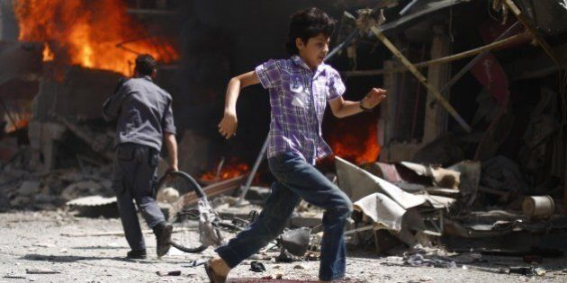 A Syrian youth runs past blood stains and debris following air strikes by government forces on the rebel-held...