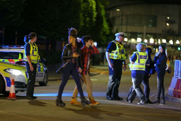 Concert-goers leave the Manchester Arena following the blast as police cordon off the area in case of...