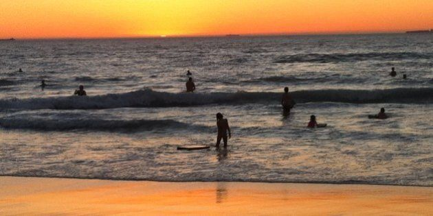 Swimmers and bodyboarders enjoy the water late at dusk during a Perth summer