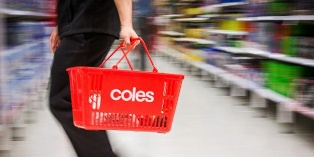 A shopper carries a basket while walking through a Coles supermarket, operated by Wesfarmers Ltd., in...