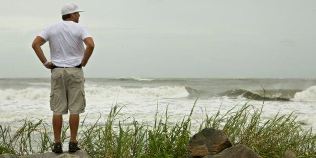 A surfer looks out over the Atlantic Ocean as the first bands of rain and wind from Hurricane Irene come ashore causing larger than normal waves at Folly Beach in Charleston, S.C., Friday, Aug. 26, 2011.  (AP Photo/Brett Flashnick)