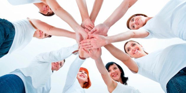 Teamwork concept. Group of women joining hands. Low angle view, white background.