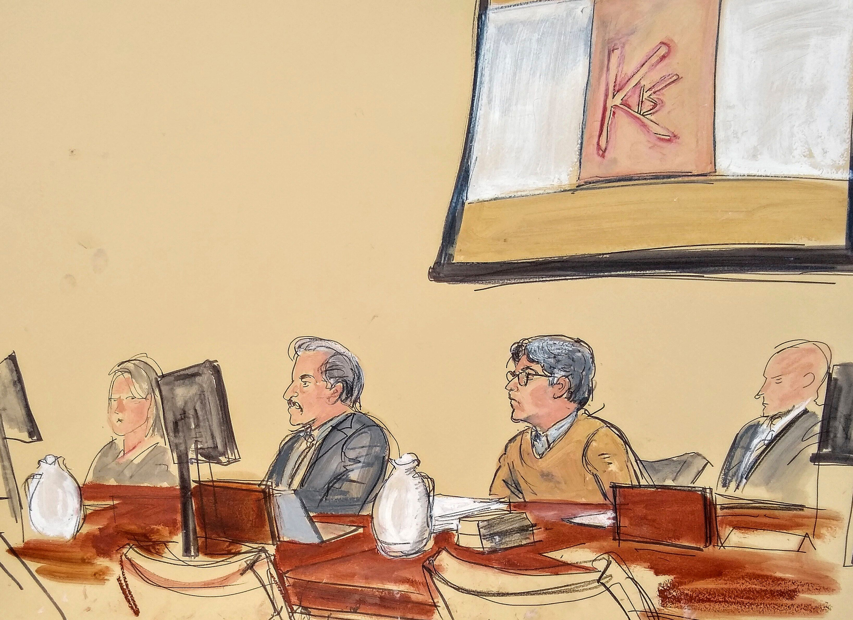 "In this courtroom artist's sketch, Keith Raniere, second from right, leader of the secretive group NXIVM, attends his trial in Brooklyn federal court, Tuesday, May 7, 2019 in New York. Above him is a screen with an image of a branding, containing his initials KR. A federal prosecutor says the self-help guru used threats, ""shame and humiliation"" while grooming women for sex. She also described how some female followers were branded with Raniere's initials. (Elizabeth Williams via AP)"