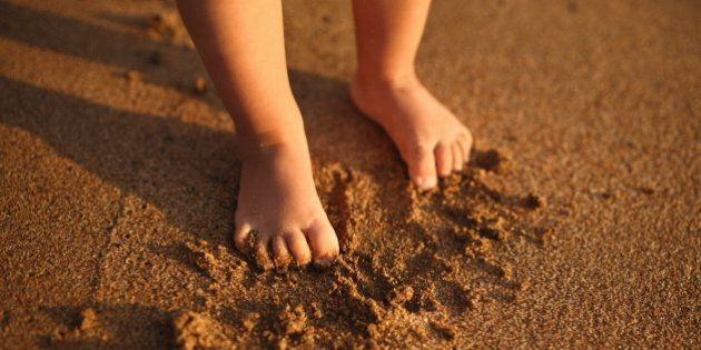 Small feets of child on sandy