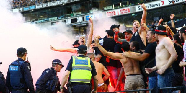 MELBOURNE, AUSTRALIA - FEBRUARY 06: Wanderers fans in the crowd let off flares as police officers look...