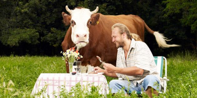 Man eating steak in field with