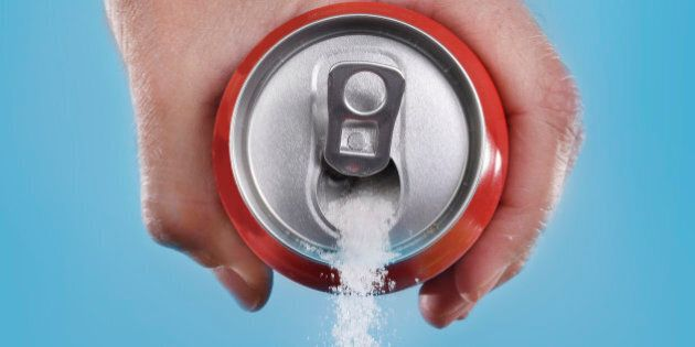 hand holding soda can pouring a crazy amount of sugar in metaphor of sugar content of a refresh drink...