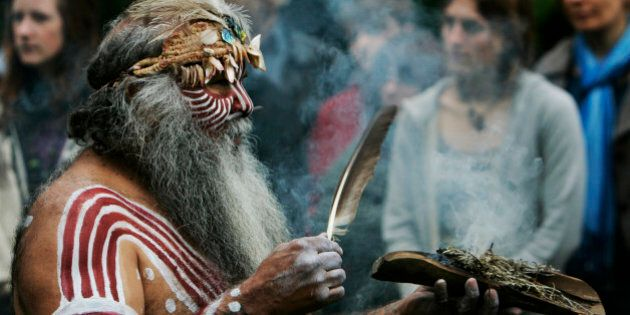 Aboriginal Ngarrindjeri elder Major Sumner from south Australia, in traditional costume, performs a ritual during a ceremony to mark the return of Australian indigenous people's remains back to their homeland,  in a central London park, Thursday May 14, 2009. A skull and other bone fragments uncovered in the basement of an elderly British academic's home have been handed over to the Australian government in a solemn Aboriginal ceremony held in a central London park. They're the latest batch of bones to be returned to the country, part of Australia's ongoing effort to recover Aboriginal remains scattered in museums and hidden away in cupboards all over the world. (AP Photo/Lefteris Pitarakis)