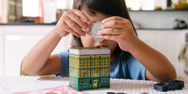A child places Australian coins into a piggy bank