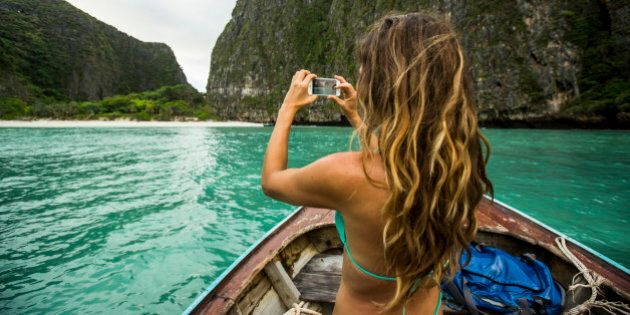 A woman taking a photo while riding on a long tail boat to a tropical island in