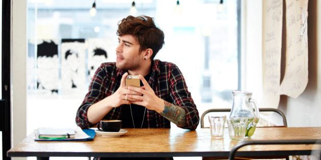 Guy with phone relaxing in coffee