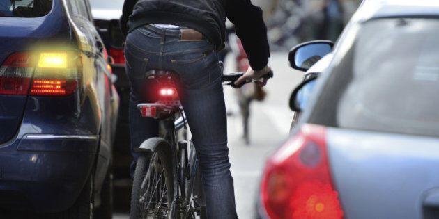 Male bicyclist in heavy traffic