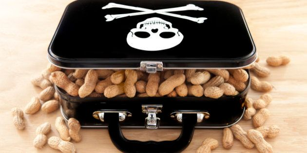 Black lunchbox with skull and crossbones on lid and peanuts overflowing out of