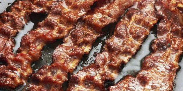 Bacon slice being cooked in frying pan. Close