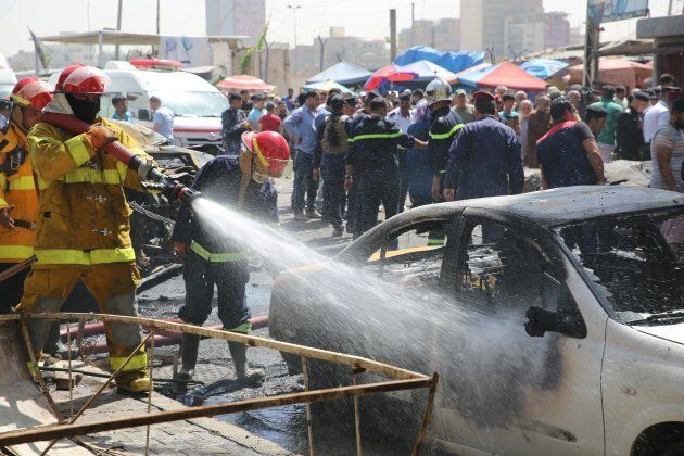 Firefighters work to extinguish the wreckage following a car bomb attack near a government office in...