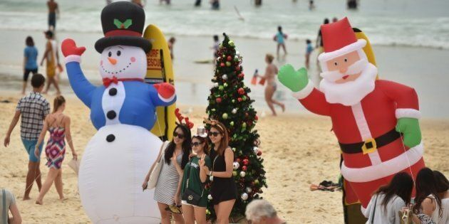 Visitors take photos in front of an inflatable snow man and Santa Claus on Bondi Beach on Christmas Day,...