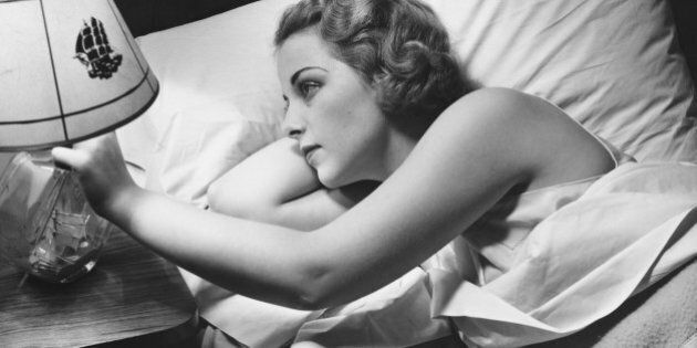Young woman lying on bed, turning off lamp on night table (B&W), elevated