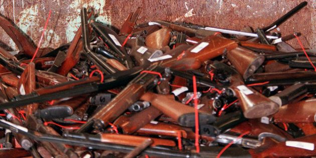 TO GO WITH US-shooting-guns-Australia,FOCUS by Martin Parry(FILES) This file photo taken on July 28, 1997 shows a policeman responsible for the collection of guns, Mick Reolandts, holding a military type shotgun, one of 4,500 guns on display before being melted down in Sydney after Australia banned all automatic and semi-automatic rifles in the aftermath of the Port Arthur shooting in 1996.  When Martin Bryant massacred 35 people with semi-automatic weapons at Port Arthur in 1996, then-Australian prime minister John Howard reacted swiftly by pushing for tough new national gun laws. Within a year gun licences had been tightened, a weapons buy-back was enacted and an amnesty launched for anyone holding illegal arms, moves that took more than 600,000 guns out of action.            AFP PHOTO / FILES / WILLIAM WEST        (Photo credit should read WILLIAM WEST/AFP/Getty Images)