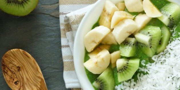 Green smoothie bowl with spinach, fresh kiwi fruit, bananas and coconut on a slate background