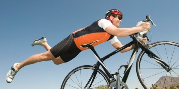 Male cyclist balances his stomach on bicycle