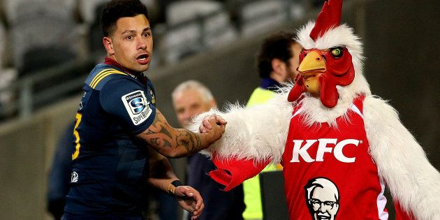 The Highlanders' Rob Thompson celebrates his try with the KFC mascot in a Super Rugby Match in