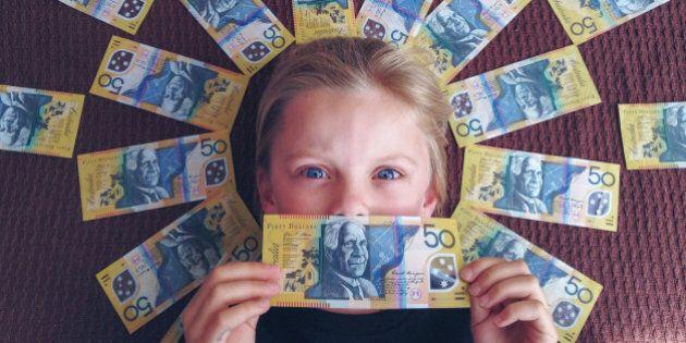Child holding onto and surrounded by large amount of Australian money