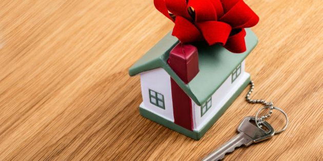 house with red ribbon and key on wooden