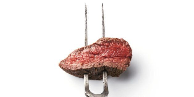 Piece of beef steak on meat fork on white