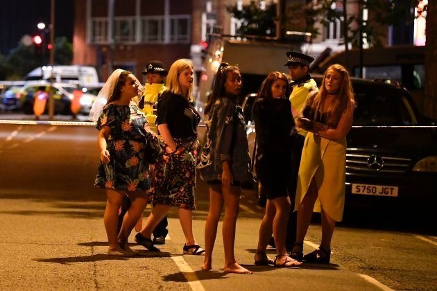 Women stand at a police cordon set up in London.