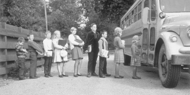 Line of children at bus stop getting on the school bus, Birmingham, Michigan, November 5, 1966. (Photo...