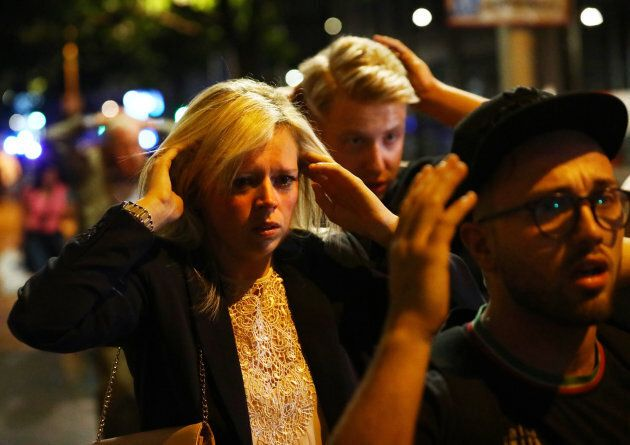 People leave the area with their hands up after an incident near London