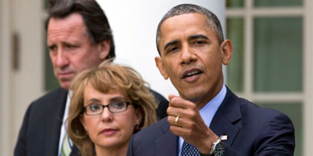 In this photo from Wednesday, April 17, 2013, Neil Heslin, father of six-year-old Newtown victim Jesse Lewis, left, and former Rep. Gabby Giffords, D-Ariz., stands by President Barack Obama as he gestures while speaking during a news conference in the Rose Garden of the White House in Washington. In past five years, Giffords has hiked the Grand Canyon, raced in a 40-mile bike ride, sky dived and founded an advocacy group that helped convince President Obama to take executive action on gun control.   (AP Photo/Jacquelyn Martin)