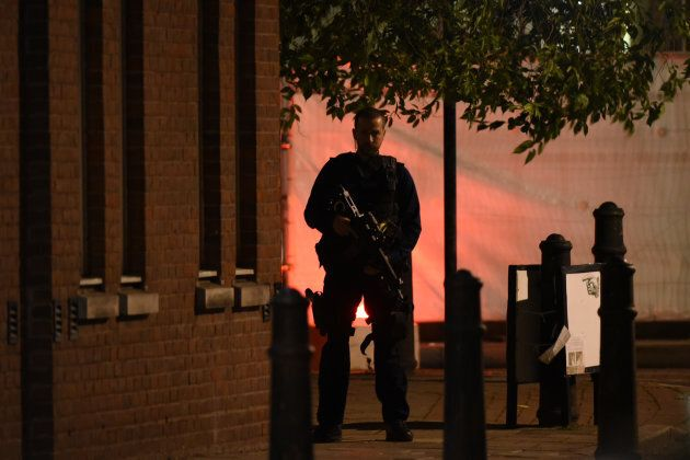 An armed police officer stands guard on a corner.