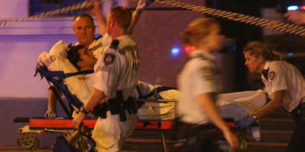 (AUSTRALIA & NEW ZEALAND OUT) An injured man is taken to hospital by ambulance officers at Hickson Road...