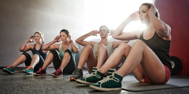 Four young women fitness training, doing sit-ups together in urban industrial