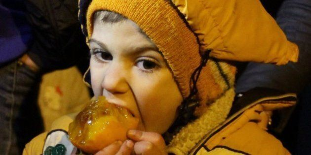 A Syrian child eats a fruit on the outskirts of the besieged rebel-held Syrian town of Madaya, on January...