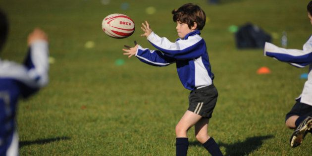 Young boy receiving a pass in a rugby training session on a grass