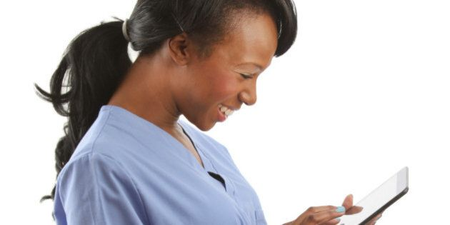 African American nurse laughing with touch pad
