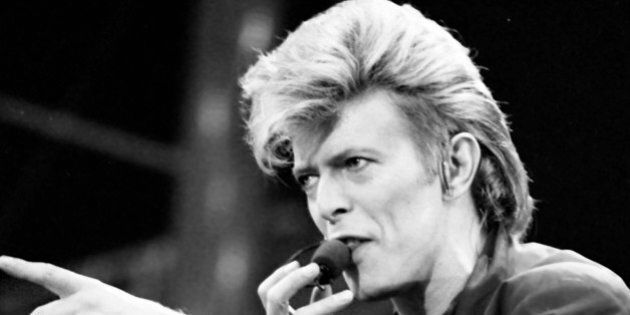 David Bowie sings and points toward the crowd during his concert at Wembley Stadium on Saturday, June...