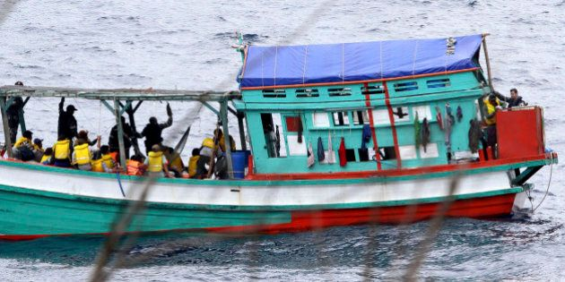In this photo taken on April 14, 2013, a fishing boat carrying Vietnamese asylum seekers nears the shore...