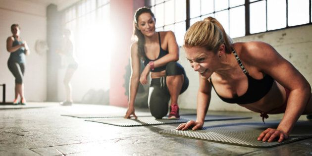 Healthy woman fitness training, doing press-ups with determined expression in urban industrial gym. Friend is giving encouragement beside her whilst other females workout in background.