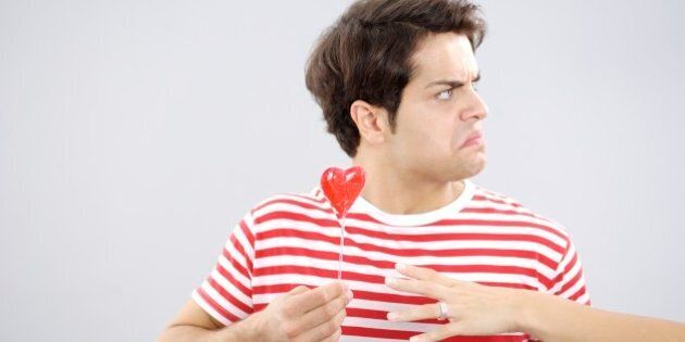 Upset man in red striped shirt with heart lollipop
