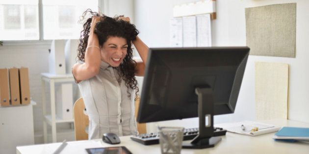 Mixed race businesswoman frustrated at computer at desk in office
