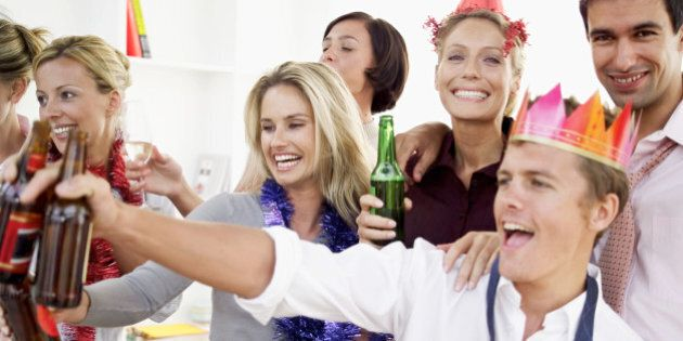 close-up of co-workers celebrating with beers at a office